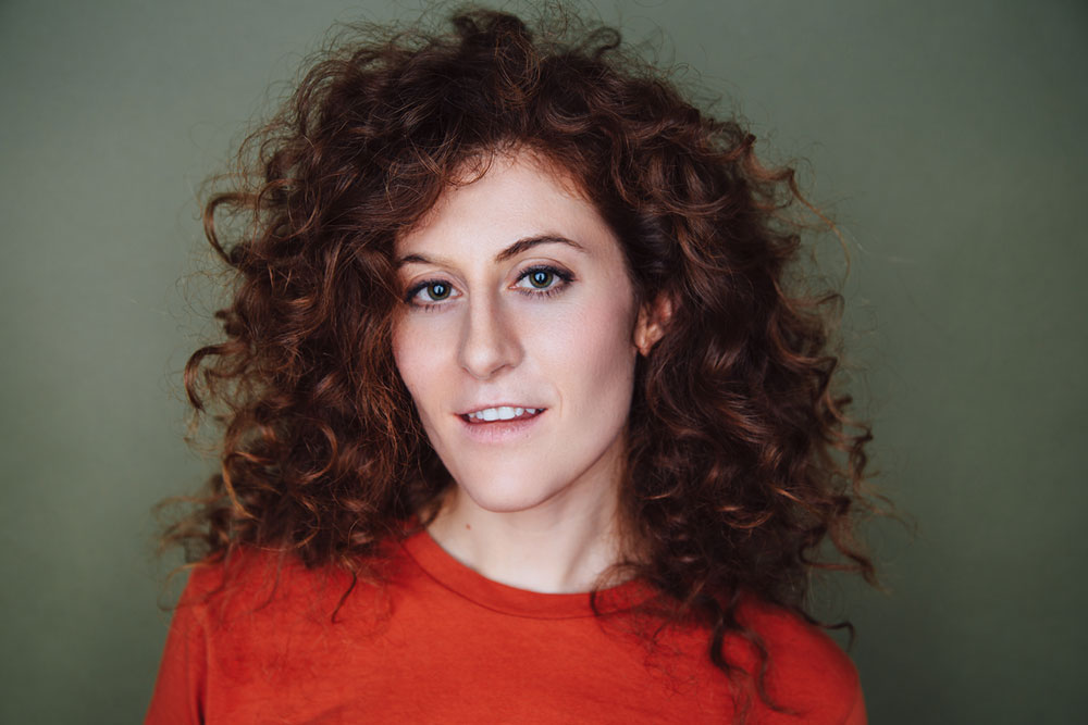 Suzie Léger, headshot with orange shirt and curly hair
